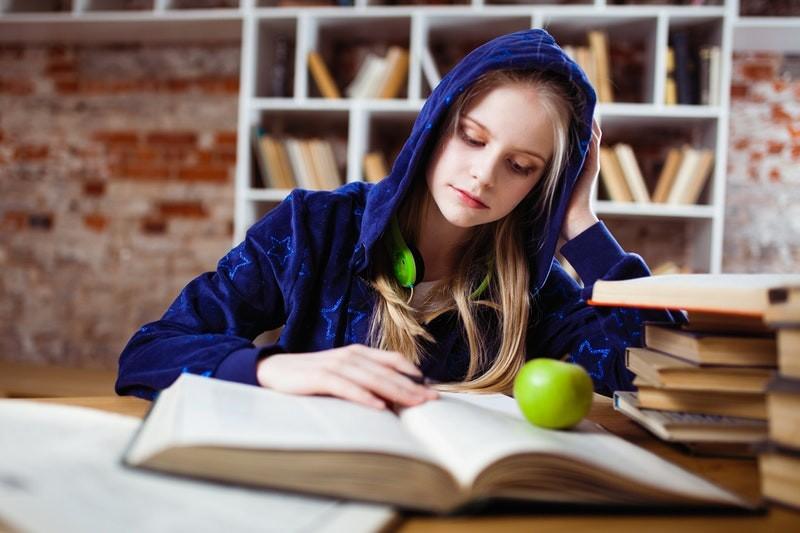 Meisje met blauwe trui leest een leuk jeugdboek
